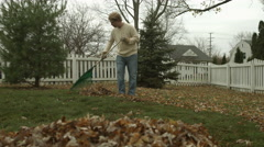Teenager rakes autumn leaves into a pile 4K - stock footage