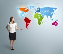 Young woman presenting colorful world map - stock photo