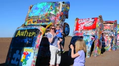 Amarillo Texas famous Cadillac Ranch child spraying paint off of Route 66 old Stock Footage