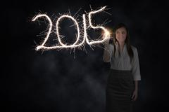 Stock Photo of Composite image of businesswoman touching spark