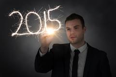 Stock Photo of Composite image of businessman touching spark