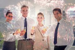 Composite image of smiling team of business people honoring a success with Stock Photos