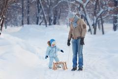 Child sits on the sledge, his father waits - stock photo