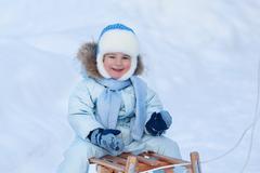 Stock Photo of Portrait of cute boy on a sledge in winter