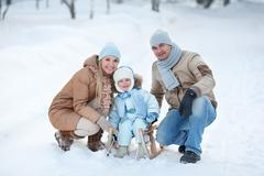 Portrait of young family in a winter park - stock photo