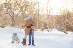 Stock Photo of Young family hugging in the park