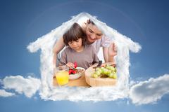 Composite image of jolly mother and her child having breakfast - stock photo
