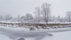Up  Over frozen trees and river.  Winter Aerial shot in 2.7K (2704x1524) Stock Footage