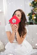 Composite image of brunette showing gift on the couch at christmas Stock Photos