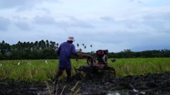 Ploughing machine harrows rice field Stock Footage