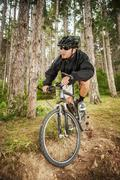 Mountain biker on pathway in forest Stock Photos