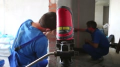 Two workers make measurements with laser level tool Stock Footage
