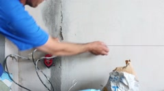 Worker checks accuracy of marking lines on wall with thread - stock footage