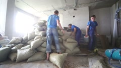 Workers throw bags and third worker carries canisters Stock Footage