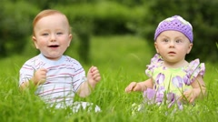 Beautiful boy and girl sit on fresh green grass of meadow Stock Footage