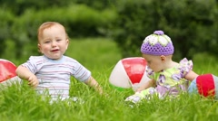 boy and girl play with balls on fresh green grass of meadow - stock footage