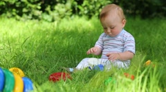 Beautiful baby plays with toys on fresh green grass of meadow Stock Footage
