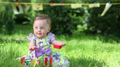 Stock Video Footage of baby plays with wooden metallofon on green grass