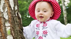 Cute baby in red hat and white blouse holds on to tree Stock Footage