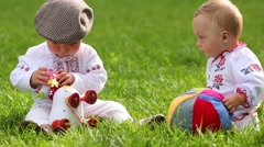 Two cute babies in folk clothes play with toy cow and ball Stock Footage