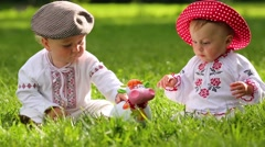 Two cute babies in folk clothes play with toy funny cow on grass Stock Footage