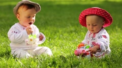 Two babies in folk clothes and hats play with toy funny cow Stock Footage