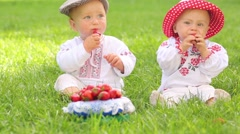 Two cute babies in folk clothes and hats eat strawberries Stock Footage