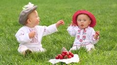 Two babies in folk clothes play near red strawberries on grass Stock Footage