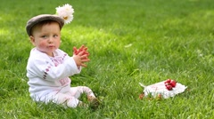 Cute baby in folk clothes and cap play with strawberry on grass Stock Footage