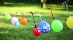 Many children balloons hang on clothesline on wind at summer park Stock Footage