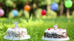 Two cakes with burning candles and balloons hanging on clothesline Stock Footage