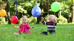 Balloons hang on clothesline and two babies play with its Stock Footage