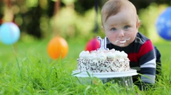 Cute baby eats cake with candle in form of 1 at summer park - stock footage