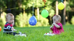 Two stained babies eat cakes with candles in form of 1 Stock Footage