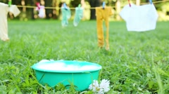 Wet clothes hang on clothesline and basin with foam stands Stock Footage