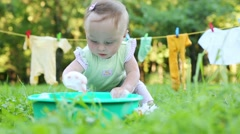 Baby touches and eats foam in basin on grass Stock Footage