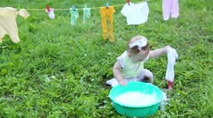 Baby washes clothes and touches foam in basin on grass Stock Footage