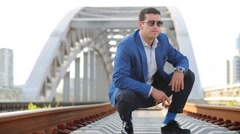 Young man in sunglasses squats and takes stones on railway bridge Stock Footage