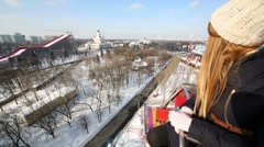 Young woman looks down on ferris wheel at winter day Stock Footage