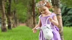 Little girl in beautiful violet gown and crown holds handbag Stock Footage