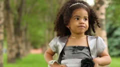 Little biracial girl in grey dress stands in park and looks around Stock Footage