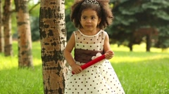 Little biracial girl in dress stands in park with big red pencil Stock Footage