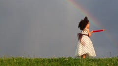 Biracial girl in dress stands with big red pencil looks at rainbow Stock Footage