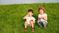 Two children with hearts on shirts sit on grass and eat candy Stock Footage