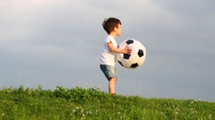 Stock Video Footage of Little cute boy carries inflatable soccer ball on green meadow