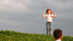 Little happy boy and girl in white t-shirts play on green meadow Stock Footage