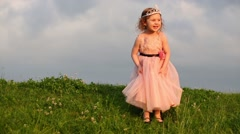 Little cute girl in pink dress touches skirt on green meadow Stock Footage