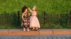Girls stand on curb next to forged fence and correct hairstyle Stock Footage