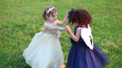 Two little girls in beautiful dresses dance on green grass - stock footage