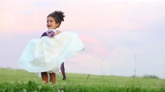Little cute girl in white dress touches skirt on green meadow Stock Footage